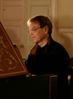 Charles Sherman sitting at a harpsichord with one ray of sunlight hitting him on the forehead
