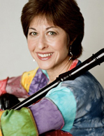 Judith Linsenberg sitting with a recorder propped jauntily on her shoulder, wearing a multicolor striped top.